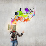 Reading concept. Woman in casual wear hiding her face behind book Stock Images