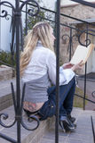 Reading Concepts and Ideas. Portrait of Tranquil Caucasian Blond Female With Book Sitting on Stairs Outdoors and Reading Stock Photography