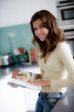 Reading Cookbook. A young woman reading a cookery book in the kitchen royalty free stock photography