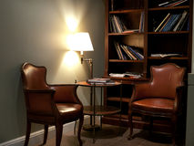 Reading corner. Library with fine art albums with two leather chairs and a round table. Yellow lamp gives a nice warm light Stock Photo