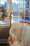 Reading corner - comfortable chair with fur throw and a rose by windows and lamp with happy sun and mirrow decor behind and. Outdoors seen through windows stock image