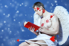 Reading Cupid. Male angel Cupid with a bow and arrows of love holds opened book. Valentine`s day. Love concept stock photography