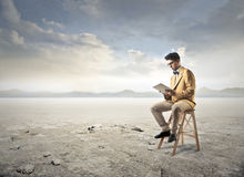 Reading in a desert Stock Photo