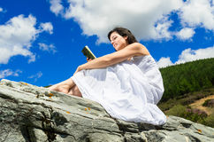 Reading diary. Young woman reads her diary in a sunny day outdoors Royalty Free Stock Photo