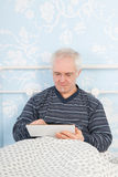 Reading digital tablet in bed Royalty Free Stock Images