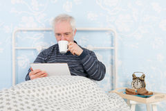 Reading digital tablet in bed Stock Image
