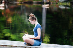 Reading on a dock Stock Image
