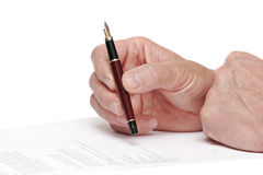 Reading a document  with a fountain pen. Someone reading a document  with a fountain pen isolated on a white background Stock Photography