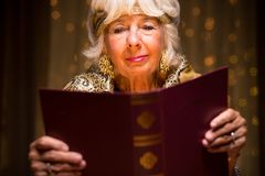 Reading a dream book. Old fortune teller is reading a dream book royalty free stock photos