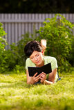 Reading e-book in the park Stock Image