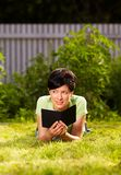 Reading e-book in the park Royalty Free Stock Photography