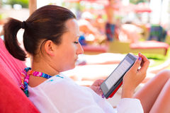 Reading on e-book on summer holidays. Woman reading on electronic book on summer holidays Royalty Free Stock Photo