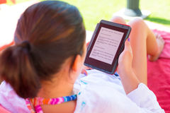 Reading on e-book on summer holidays. Woman reading on electronic book on summer holidays Royalty Free Stock Images