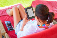 Reading on e-book on summer holidays. Woman reading on electronic book on summer holidays Royalty Free Stock Photos