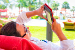 Reading on e-book on summer holidays. Woman reading on electronic book on summer holidays Stock Photos