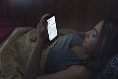 Reading an ebook in bed Stock Photography