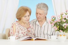 Reading elderly couple resting at home Stock Images