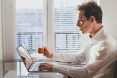 Reading emails. Businessman reading emails in the office with cup of coffee Royalty Free Stock Photos