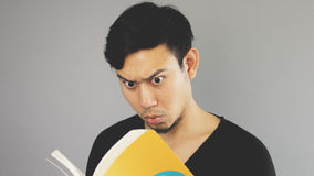 Reading exciting contents. An asian man with black t-shirt stock photos