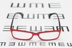 Reading eyeglasses and eye chart Royalty Free Stock Photos
