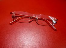 Reading eyeglasses on a red leather background. Red reading eyeglasses on a red leather background Royalty Free Stock Photography