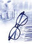reading eyeglasses with stacking of newspaper background , busin Royalty Free Stock Photos
