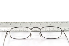 Reading eyeglasses on table with view of ruler through glasses Stock Photo