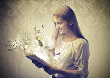 Reading a Fable. A little girl is reading a fable which is taking life royalty free stock photography