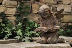 Reading Fairy Garden Statue. Statue of kneeling fairy reading a book with stone wall and green vine background Royalty Free Stock Photography
