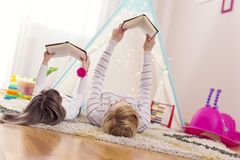 Reading a fairy tale. Mother and daughter lying on a playroom floor, reading books. Focus on the mother stock photos
