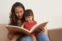 Reading fairytale. Mother reading book to her little daughter Stock Image