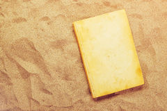 Reading favourite classic old book on summer vacation beach holi. Day, top view of a book cover as copy space in warm beach snow Royalty Free Stock Photography