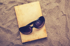 Reading favourite old book on summer vacation beach holiday. Top view of a book and sunglasses in warm beach snow Royalty Free Stock Images