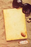 Reading favourite old book on summer vacation beach holiday. Top view of a book and sunglasses in warm beach snow Royalty Free Stock Image