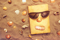 Reading favourite old book on summer vacation beach holiday. Top view of a book and sunglasses in warm beach snow Stock Photography