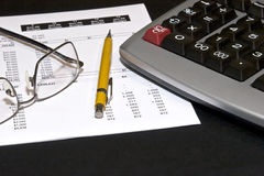 Reading financial statements. Reading glasses on top of a financial statement with a yellow pencil and a calculator Stock Photography