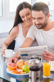 Reading fresh newspaper together. Stock Images