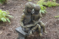 Reading is fun. A young girl and boy statue reading a book Stock Photos