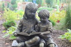 Reading is fun. A young girl and buy statue reading a book Stock Photos