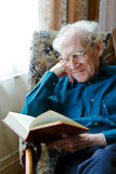 Reading Funny Book. Smiling old man in glasses reading a funny book, holding his head royalty free stock photos