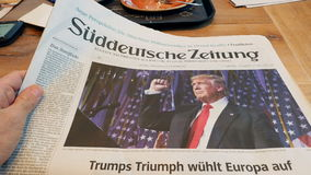 Reading in German Cafe about Donald Trump victory. FRANKFURT, GERMANY - NOV 10, 2016: POV of Man reading in German Cafe about the Suddeutsche Zeitung