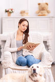 Reading girl in the armchair and her dog around Stock Image