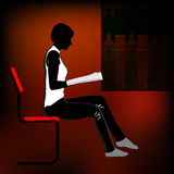 Reading girl. Girl reading a magazine while sitting on a chair Stock Photo