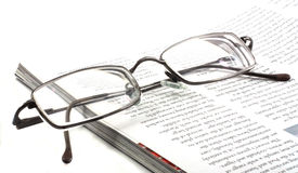 Reading glasses. A pair of glasses on an open magazine isolated on a white background stock photo