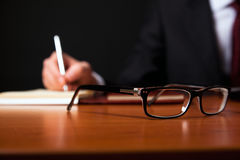 Reading glasses. On a wooden office desk. Businessman writing on the background. Selective focus on the glasses royalty free stock photos