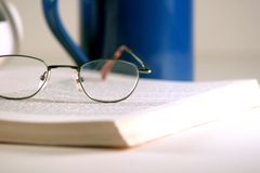 Reading glasses. Resting on a book Stock Photos