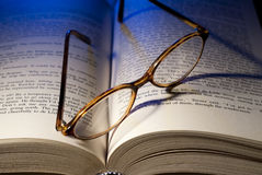 Reading glasses. On open book with blue light in background Stock Photo