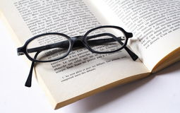 Reading glasses and book. Black glasses on an open book Royalty Free Stock Photo