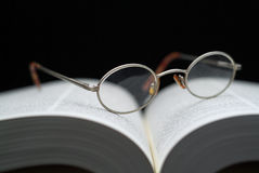 Reading glasses on book. Closeup of reading glasses on large book shallow focus royalty free stock image