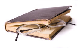 Reading - glasses in a book. Reading - glasses on an open obsolete book isolated Royalty Free Stock Photo